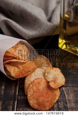 Bowl with potato crisps chips and olive oil on wooden board. Junk food