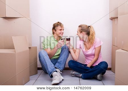 young couple celebrate in their first new home