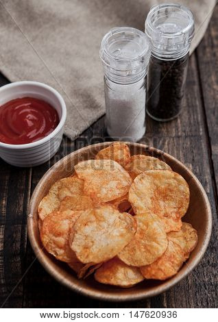 Bowl with potato crisps chips on wooden board. Salt and pepper on background