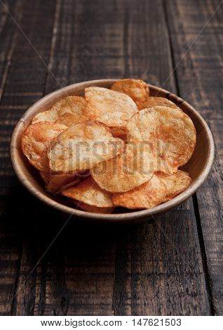 Bowl with potato crisps chips on wooden board. Junk food