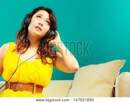 Young people leisure relax concept. Teen cute girl yellow dress in headphones listening music mp3 sitting on couch relaxing green blue background