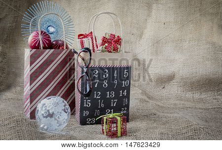 horizontal image of two different christmas bags filled with decorations and gifts with a clear christmas ball lying beside the bags on brown burlap background with copy space