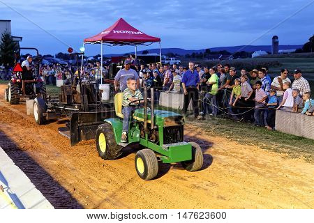MYERSTOWN PENNSYLVANIA - SEPTEMBER 16 2016: A young boy drives a modified lawn tractor at Myerstown East End Days. The tractor pull is an annual community event.