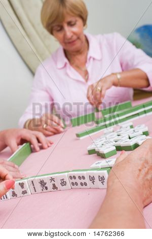 elderly lady playing mahjong game with friends