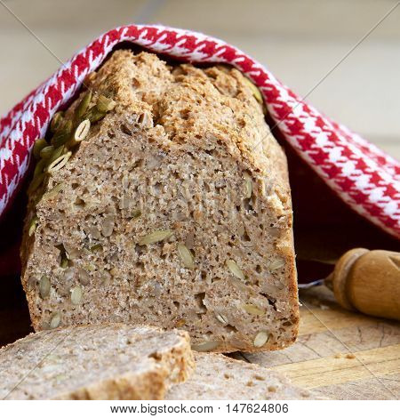 A loaf of wholemeal spelt bread with slices.
