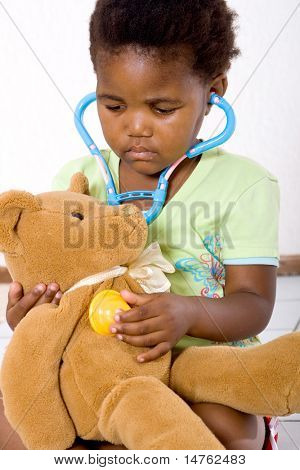 cute african american little girl playing doctor with teddy bear