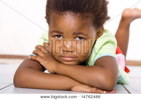 african american little girl lying on floor
