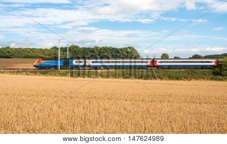 Fast passenger train in motion passing countryside