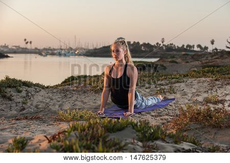 Yoga workout on marina shore in Cobra pose.