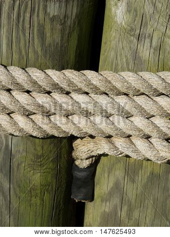 Sturdy rope binds two upright wooden posts together.
