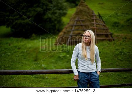 Beautiful blonde on a background of blue sky. Beautiful girl enjoying the nature. Breathing the fresh mountain air