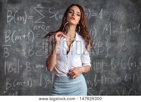 young sexy desire woman teacher near blackboard with maths formula