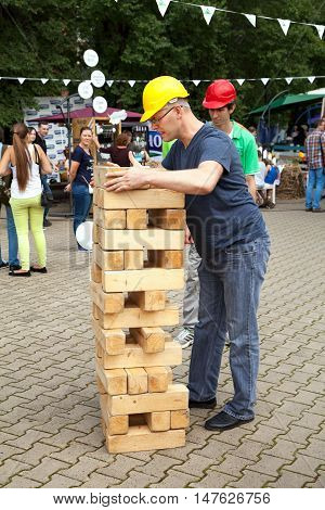 Khabarovsk Russia - September 4 2016: Contractor man playing game outdoors. Big large giant jenga competition