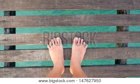 Woman's feet standing on wooden bridge over sea. Vacation holiday enjoying sun on sunny summer day concept.