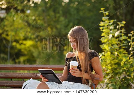 Young attractive girl drinks coffee and keeps the tablet pc. She watches the news on social networks and blog is online. A successful blogger.