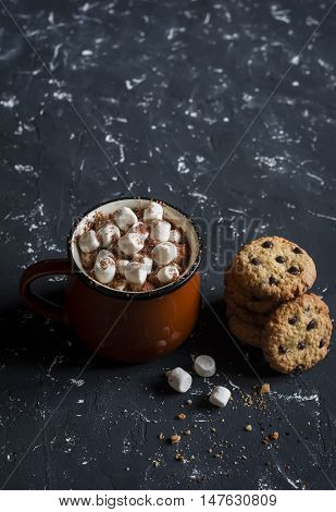 Hot chocolate with marshmallows and chocolate chips oatmeal cookies on a dark background.