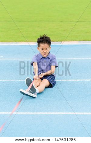 Young Asian Boy Pull A Rope On Blue Track In The Stadium