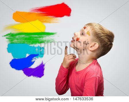 Little boy thinking reflects or makes a choice. The spots of paint on his face. Dabs of paint on the wall colors of the rainbow