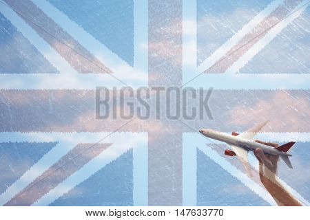 Toy plane flying in front of Union Jack flag