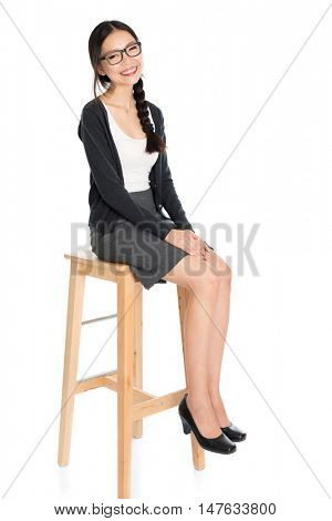 Full body portrait of young Asian woman sitting on high chair, isolated on white background.