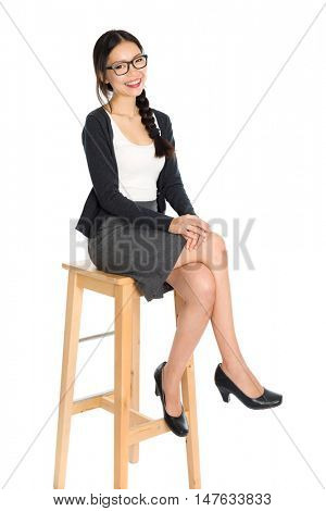 Full body portrait of young Asian woman leg crossed sitting on high chair, isolated on white background.