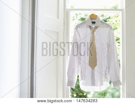 Dress shirt and tie on hanger at domestic window
