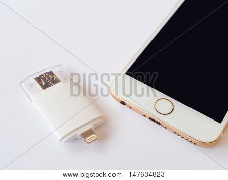CHINGRAI THAILAND -SEPTEMBER 7 2016: Close-up image of two way external flash storage (Lightning and USB) and Apple iPhone 6 isolate on white background.