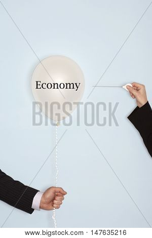 Cropped hands holding needle and popping balloon against light blue background with the text saying Economy