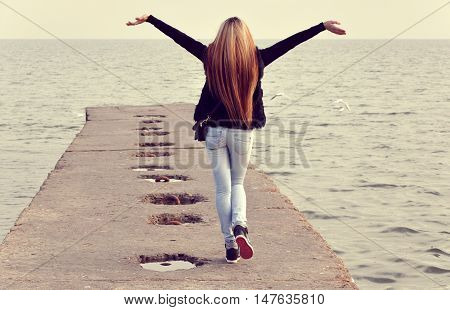 Beautiful girl walking on the breakwater in the background of the sea in autumn day.