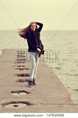 Beautiful girl walking on the breakwater on the sea background autumn day.
