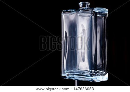 Rectangular transparent bottle of cologne isolated on a black background.