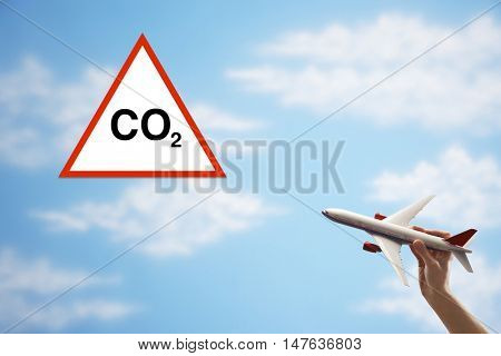 Closeup of woman's hand flying toy plane against cloudy sky