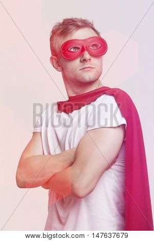 Young man in red superhero costume looking up over gray background