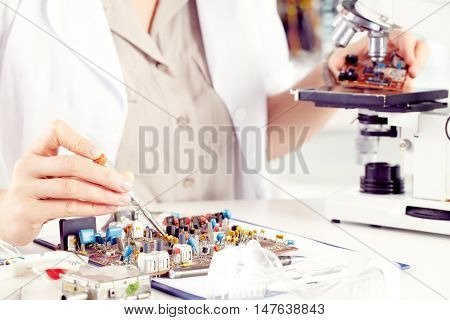 Close-up of female hands working with transistor