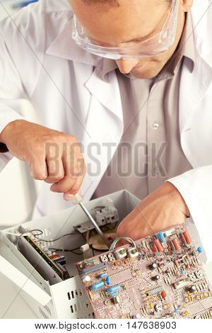 Young engineer with screwdriver examining circuit board