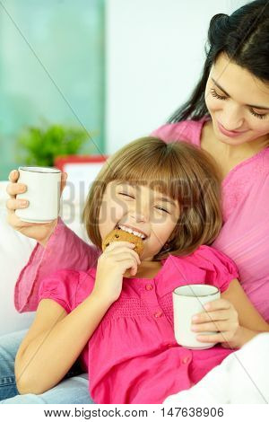 Daughter sitting on her mothers laps and eating cookie with tea