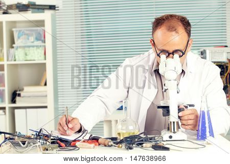 Lab technician looking through a microscope and writing results in laboratory