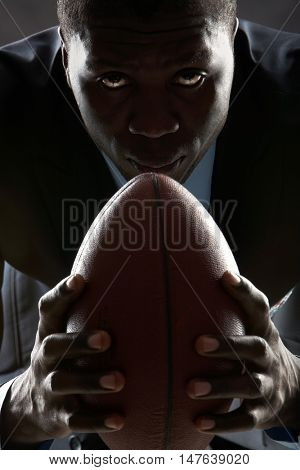 Serious man with rugby ball looking at camera