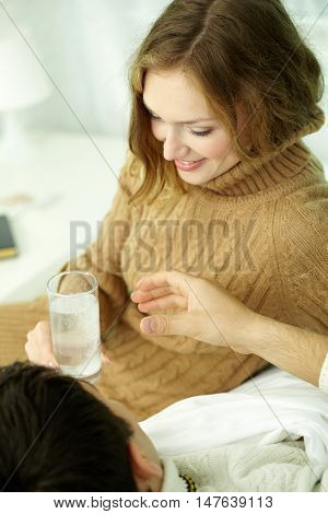 Woman taking temperature of her ill husband