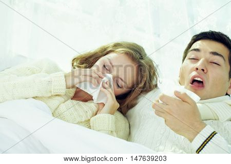 Young couple sneezing and blowing their noses