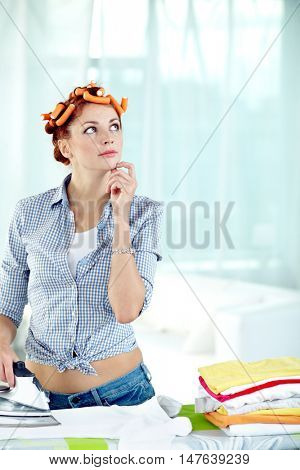 Attractive woman in curlers ironing clothes