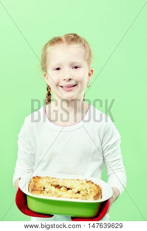Portrait of little girl with apple pie looking at camera and smiling