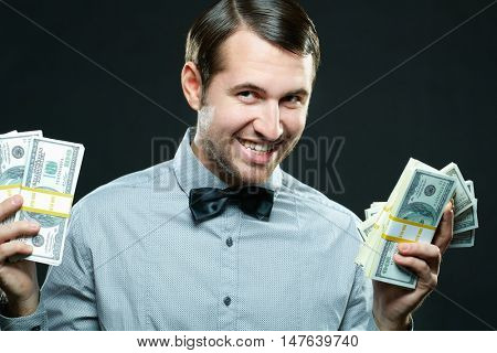 Young businessman fans out a large number of dollar bills while smiling at the camera