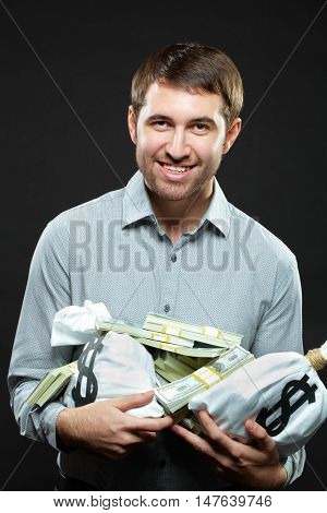Happy man holding a lot of money and looking at camera