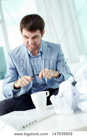 Angry businessman working with papers at the table