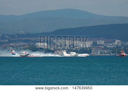Gelendzhik Russia - September 8 2010: A pair of Beriev Be-200 amphibian planes is taking off from water surface of the bay