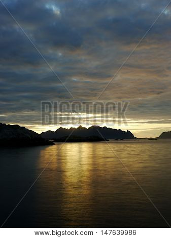 Lofoten. Sunrise over the sea behind the clouds.