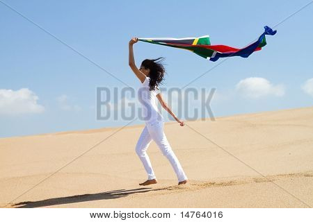 young woman running on beach and holding a south african flag