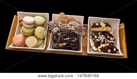 Stylish plate with various festive cookies on the dark background. Symbolic food. Confectionery scene.