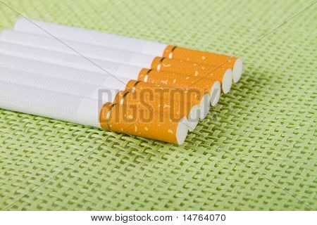 Filter cigarettes on green background